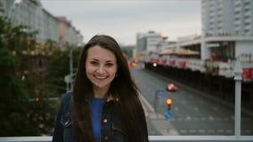 站立在桥梁,看看的美丽的女孩城市,然后转向照相机和微笑 风吹她的头发 缓慢的mo 股票录像