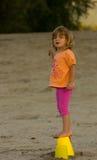 站立在桶的海滩的女孩 免版税图库摄影