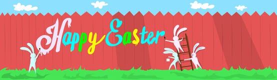 站立在梯凳举行刷子油漆愉快的复活节墙壁假日横幅的兔子小组 库存照片