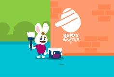 站立在梯凳举行刷子油漆愉快的复活节墙壁假日横幅的兔子小组 免版税图库摄影
