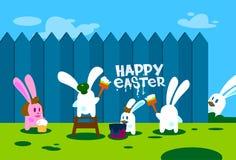 站立在梯凳举行刷子油漆愉快的复活节墙壁假日横幅的兔子小组 库存图片