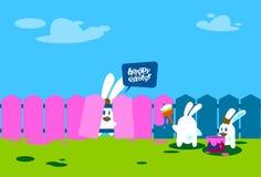 站立在梯凳举行刷子油漆愉快的复活节墙壁假日横幅的兔子小组 免版税库存照片