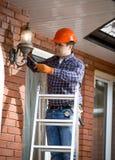 站立在梯子和改变的室外灯的电工 免版税库存图片