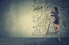 站立在梯子和画的经营计划想法的女实业家 免版税库存图片