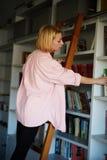 站立在梯子的迷人的金发妇女在书架,当采摘书时 库存照片