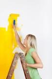 站立在梯子绘画的妇女 免版税库存照片