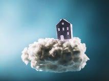 站立在棉花云彩的纸房子 免版税库存图片