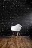 站立在棕色木地板上的屋子里的白色椅子在黑砖墙 免版税库存图片