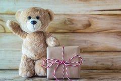 站立在棕色礼物盒旁边的玩具熊 库存照片