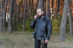 站立在森林和嗅里的皮夹克和裤子的摩托车骑士花 库存图片