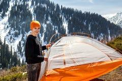 站立在森林积雪覆盖的山背景的一个帐篷附近的美丽的旅游女孩  图库摄影