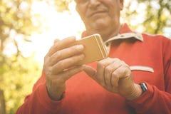 站立在森林里和使用巧妙的电话的老人 Foc 库存照片