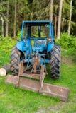 站立在森林里的一台蓝色拖拉机 免版税库存照片