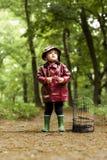 站立在森林里的小女孩寻找她失去的鸟 免版税图库摄影