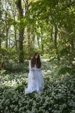 站立在森林里的长的白色礼服的美丽的妇女 免版税库存图片