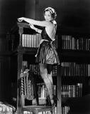 站立在椅子和拂去在性感的成套装备的一个少妇的画象一个书架的灰尘(所有人被描述不是更长的livin 库存图片