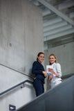站立在楼梯和使用数字式片剂的女实业家 免版税库存照片