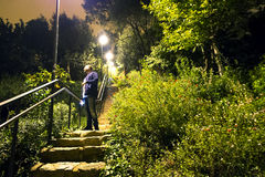 站立在楼梯的年轻人在Guell公园在晚上在光下 免版税库存照片