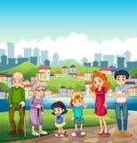 站立在横跨村庄的河岸的一个大愉快的家庭 免版税库存照片