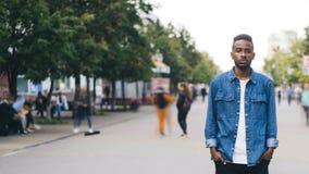 站立在步行街道的孤独的非裔美国人的人学生定期流逝在大城市用在口袋的手和 股票录像