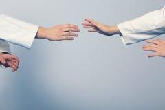站立在武术训练的姿态的两个女孩的手 免版税库存照片