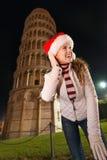 站立在比萨斜塔附近的圣诞老人帽子的微笑的妇女 免版税库存照片