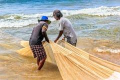站立在水中的渔夫被拉扯对网络的岸与一风行的一个晴天 免版税库存照片