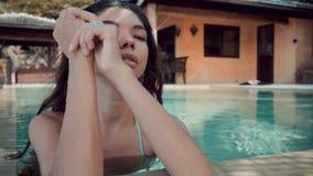 站立在水池的边缘在别墅的和看照相机的比基尼泳装的年轻魅力妇女 股票录像