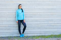 站立在水泥水泥墙壁前面的年轻人、适合和运动的女孩 健身,体育,都市跑步和健康 库存图片