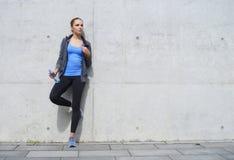 站立在水泥水泥墙壁前面的年轻人、适合和运动的妇女 健身,体育,都市跑步和健康 图库摄影