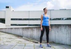 站立在水泥水泥墙壁前面的年轻人、适合和运动的妇女 健身,体育,都市跑步和健康 库存照片