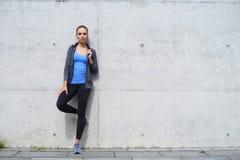 站立在水泥水泥墙壁前面的年轻人、适合和运动的妇女 健身,体育,都市跑步和健康 免版税库存照片