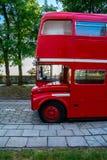 站立在江边的公园的红色两层英国公共汽车 库存图片