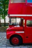 站立在江边的公园的红色两层英国公共汽车 免版税库存照片
