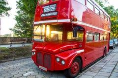 站立在江边的公园的红色两层英国公共汽车 库存照片