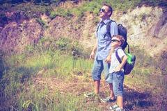 站立在池塘附近的父亲和儿子在天时间 库存图片