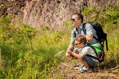 站立在池塘附近的父亲和儿子在天时间 图库摄影