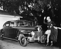 站立在汽车前面的妇女拿着袋子圣诞节礼物(所有的人被描述不是更长生存和前没有的庄园 免版税图库摄影