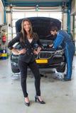 站立在汽车前面的销售妇女,为服务为deliv 图库摄影