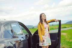 站立在汽车旁边的年轻深色的女孩 免版税库存图片