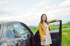 站立在汽车旁边的年轻深色的女孩 免版税图库摄影
