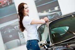 站立在汽车附近的少妇 免版税库存照片