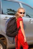 站立在汽车附近的愉快的女孩, 免版税库存图片