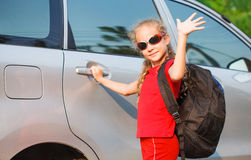 站立在汽车附近的愉快的女孩 库存图片