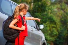 站立在汽车附近的愉快的女孩 免版税库存图片