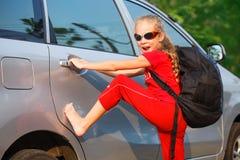 站立在汽车附近的愉快的女孩 库存照片