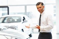 站立在汽车陈列室和显示新的汽车的推销员 库存照片