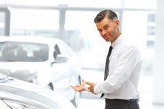 站立在汽车陈列室和显示新的汽车的推销员 免版税库存照片