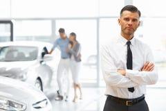 站立在汽车零售店的推销员 汽车陈列室 免版税库存图片
