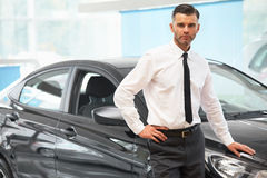 站立在汽车零售店的推销员 汽车陈列室 库存图片